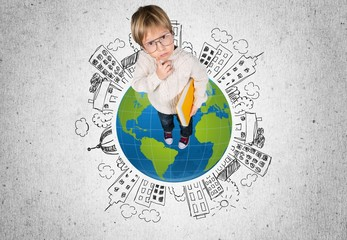 School. Clever little boy in glasses standing on abstract book
