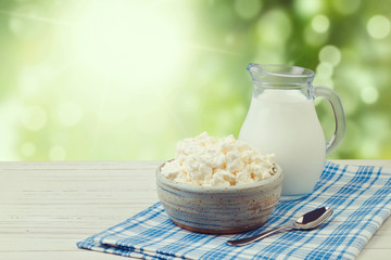 Milk and cottage cheese over green bokeh, Jewish holiday Shavuot