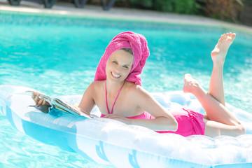 Hübsches Mädchen lächelt auf der Luftmatratze im Pool