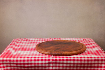 Wooden board on table with tablecloth