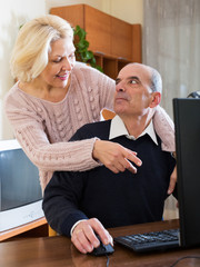 Pensioner sitting together at the computer