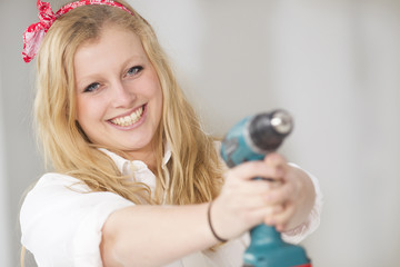 Happy young woman doing a odd-job in her new house