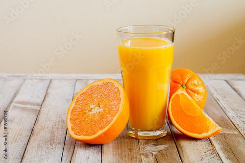Orange fruit and glass of juice on white wooden background - 81590524