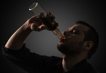 Alcoholism. Silhouette of man drinking alcohol, close up