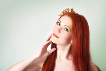 Portrait of beautiful red-haired girl with flowers in hair