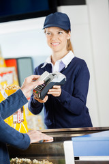 Smiling Worker Accepting Payment Through NFC Technology At Cinem