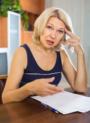 Sad woman filling financial documents