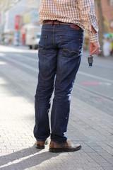 Mann mit Autosschlüssel wartet auf Straßenbahn