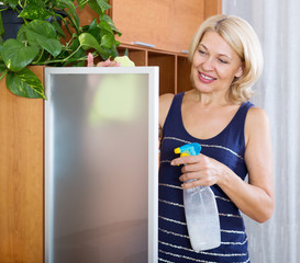 Mature woman dusting glass
