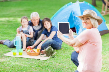 Happy Grandmother Photographing Family At Campsite