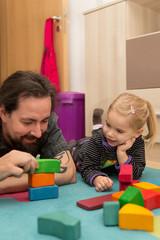 Vater und kleines Mädchen spielen mit bunten Bauklötzen