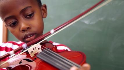 Cute pupil playing violin