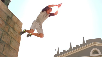 Young man jumping from wall