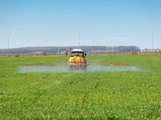tractor spreading herbicides over a green field