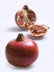 Whole pomegranate and half with seeds