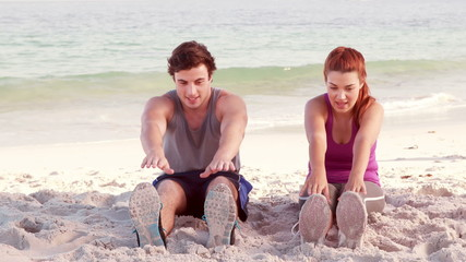 Smiling couple stretching their legs on the beach