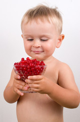 Smiling little boy with glass bowl of red currants