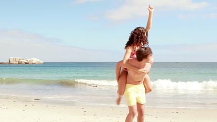 Man giving his girlfriend a piggy back at the beach