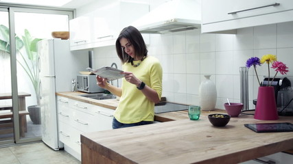 Young woman reading newspaper standing in kitchen at home