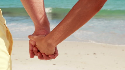 Couple on the beach looking out to sea holding hands