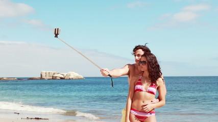 Happy couple doing selfie with monopod