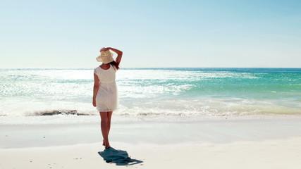 Woman in white dress walking on the beach