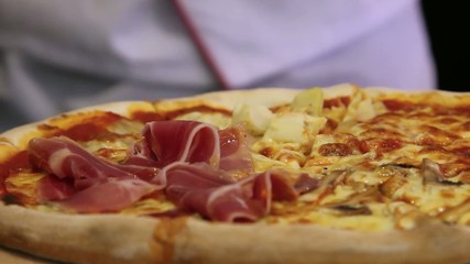 Hands chef cuts italian pizza with mushrooms, ham, pineapple and