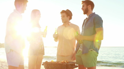 Smiling friends cooking barbecue on the beach