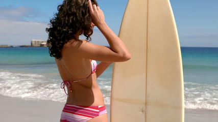Beautiful brunette standing with surfboard