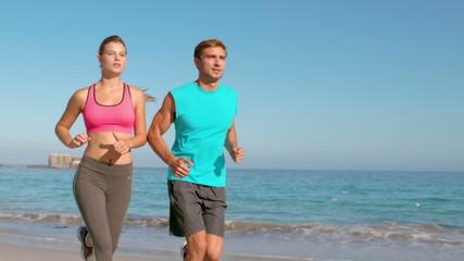 Couple jogging on beach
