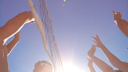 Attractive young friends playing beach volleyball
