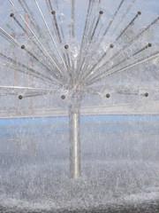 Dandelion shaped fountain in water basin