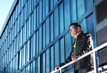 Hombre mirando lejos. Escena urbana de la Moda y edificios