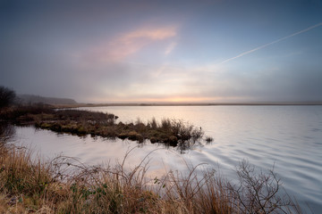 Foggy sunrise over Crowdy reservoir on Bodmin Moor in Cornwall