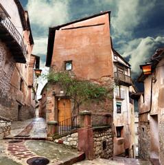 Casa surrealista y calle del pueblo de adoquines en la noche
