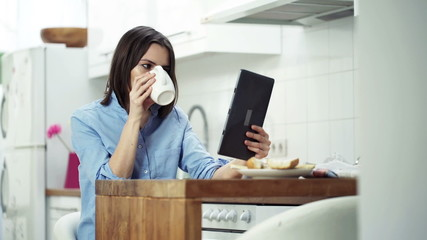 Woman reading news on tablet computer and drinking coffee