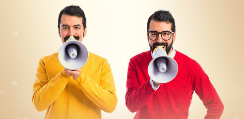 Twin brothers shouting by megaphone