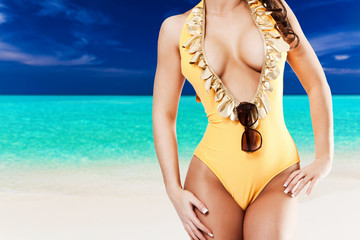 Sexy woman in yellow bikini in front of tropical beach with blue