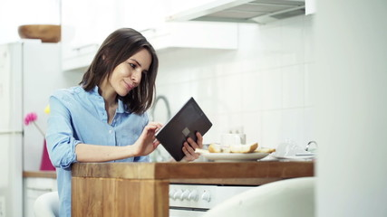 woman using tablet computer sitting by table in kitchen at home