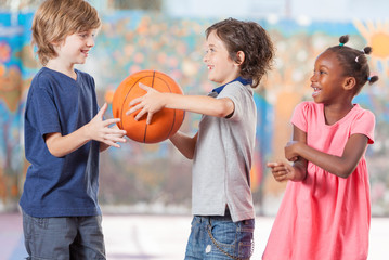 Happy multi ethnic children playing basketball at school