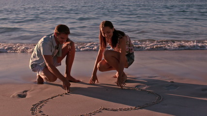 Happy couple drawing heart in the sand