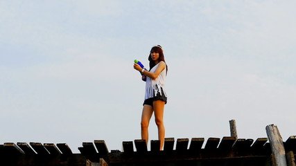 Beautiful woman with shoot a water gun. concept slow motion.