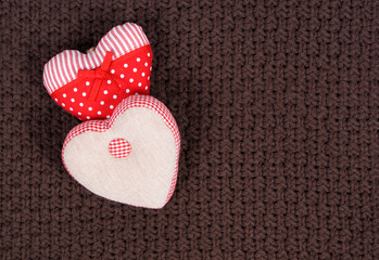 Two handmade fabric hearts on a broun knitted background