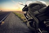 Motorbike on an empty road at sunset poster