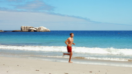 Fit man jogging on the beach