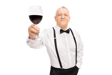 Senior gentleman proposing a toast with glass of wine