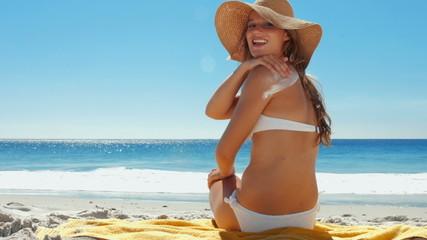 Beautiful woman putting on sunscreen at beach