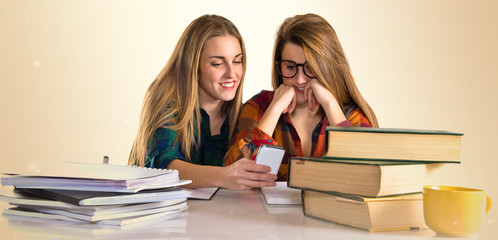 Friends playing with phone while studying