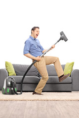 Guy playing guitar on a vacuum cleaner wand