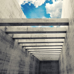 Empty interior with concrete walls, beams and cloudy sky